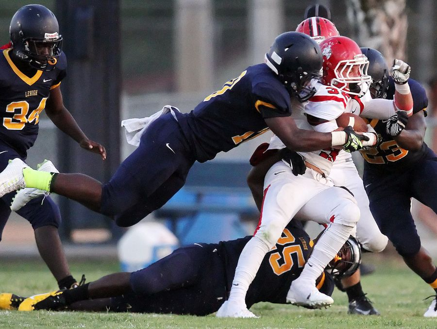 Lehigh High School defenders Yovani Tomas-Cabrera, top, and Chris Matheus, bottom, tackle North Fort Myers' ST. Amand on Friday (5/23/14) at Lehigh High School.