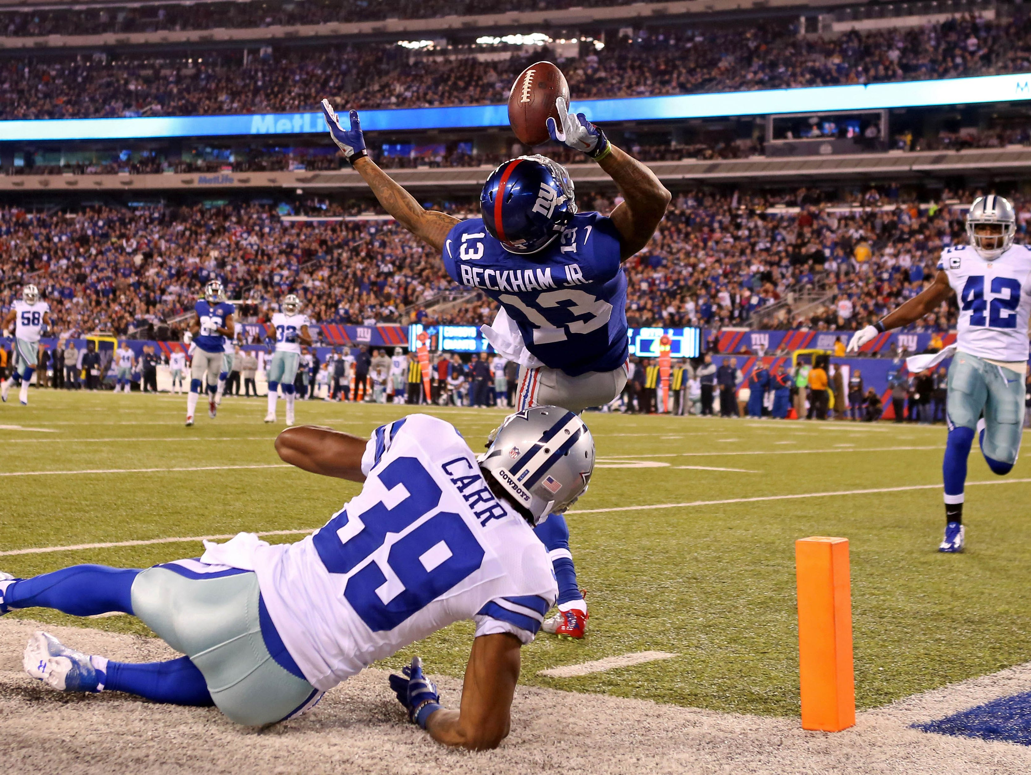 New York Giants wide receiver Odell Beckham (13) catches a touchdown pass over Dallas Cowboys cornerback Brandon Carr (39) during the second quarter at MetLife Stadium. Mandatory Credit: Adam Hunger-USA TODAY Sports