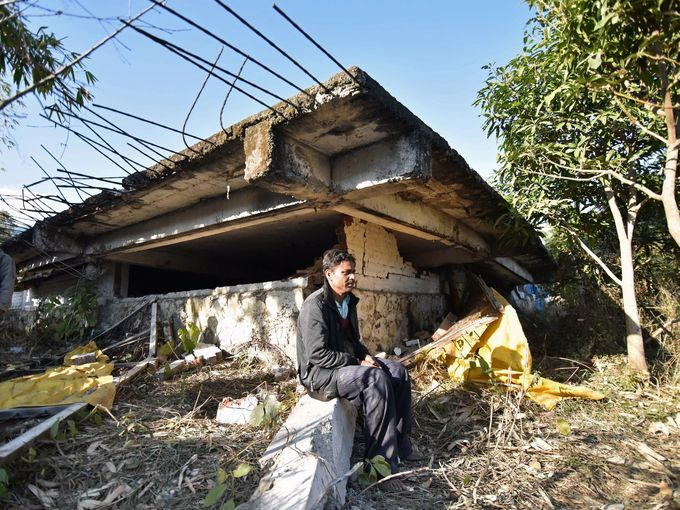 Gopal Motea sits in front of his collapsed house where