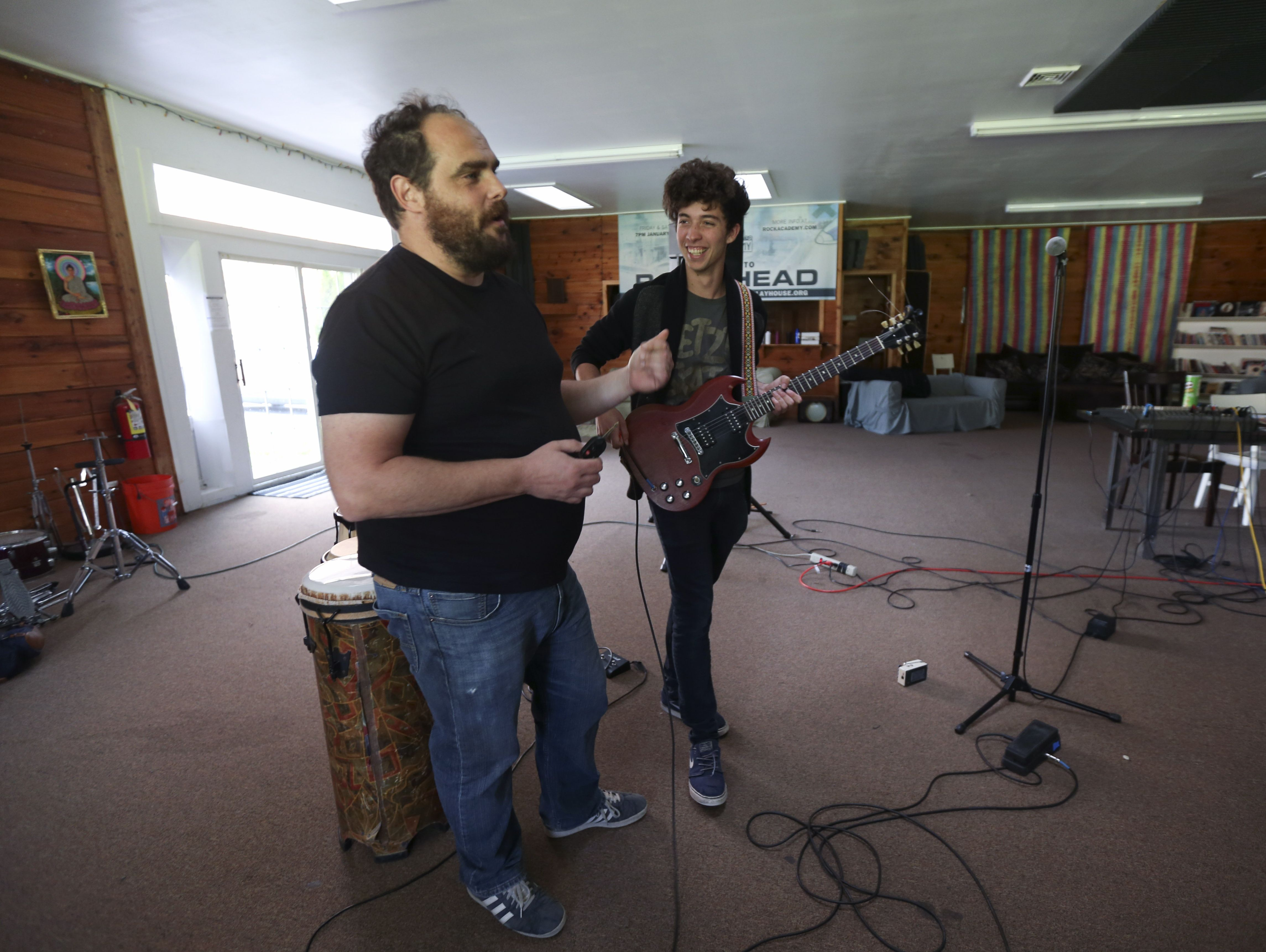 Paul Green, left, talks with student Diggy Lessard, son of Dave Matthews Band bass player Stefan Lessard, at the Paul Green Rock Academy in Saugerties.