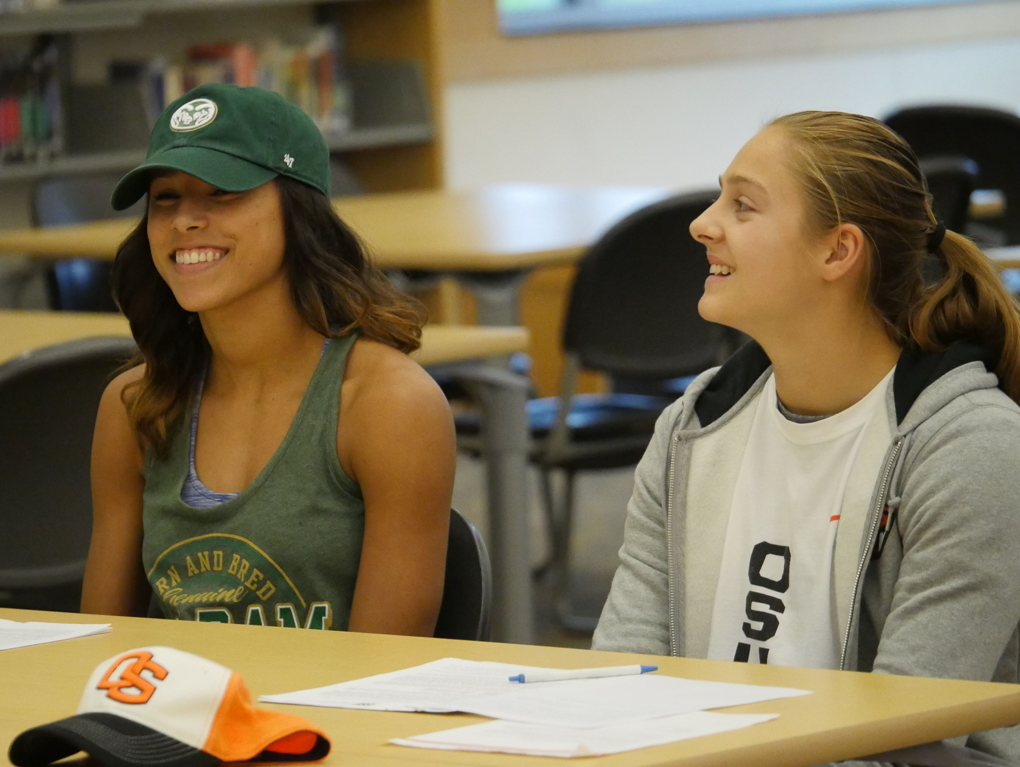 Lynnwood's Jordyn Edwards (left) and Mikayla Pivec listen to their head coaches remarks at their signing celebration.